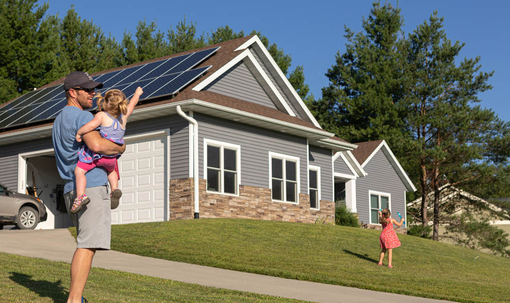 Father and daughter standing in front of house with solar panels on roof